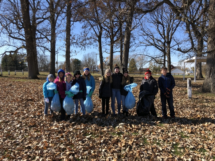 Student council members at the park, picking up litter.